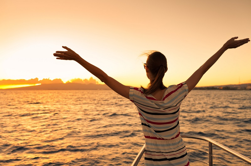 Woman,On,A,Yacht,Looking,Out,Into,The,Beautiful,Sunset